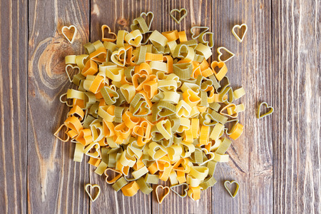food products: Durum wheat heart-shaped pasta with vegetables on wooden background for Valentine Day. Top view. Stock Photo