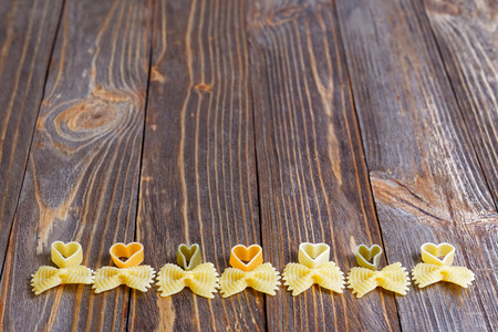 comida italiana: Fondo del alimento. Ornamento del arco de las pastas en la mesa de madera. Vista en �ngulo.