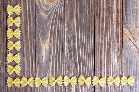 wheat: Food background. Ornament from pasta bow on wooden table. Stock Photo
