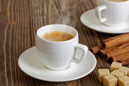 tazas de cafe: Humeante caf� espresso en una taza blanca, la canela y el az�car moreno en mesa de madera. enfoque selectivo.