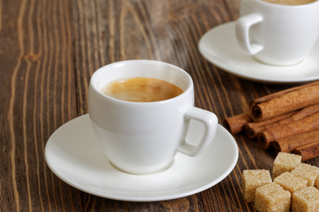 coffee mugs: Steaming espresso in a white cup, cinnamon and brown sugar on wooden table. Selective focus.