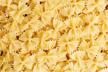 comida italiana: Food background. Pasta in the shape of a bow-tie.