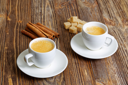 frothy: Two cup of hot espresso, cinnamon and sugar cane on brown wooden table. Selective focus. Stock Photo