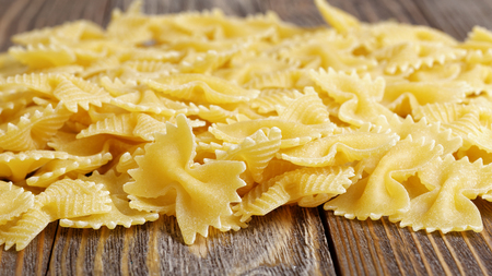 comida italiana: Pasta in the shape of a bow-tie on wooden table.