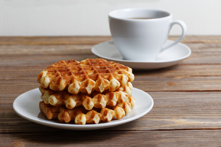 shallow  focus: Cup of tea and stack of waffles on wooden table. Shallow focus. Stock Photo