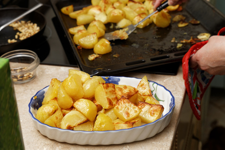 shifted: Freshly fried potatoes shifted from the pan into a dish on domestic kitchen