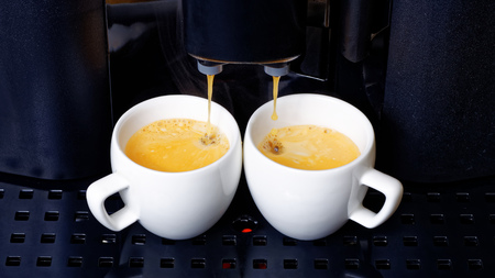 making coffee: Two white cups with espresso preparation in coffee machine
