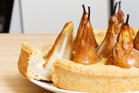 put forward: Pie with pears, cream butter and jelly on white wooden table. Put forward a piece of cake. Stock Photo