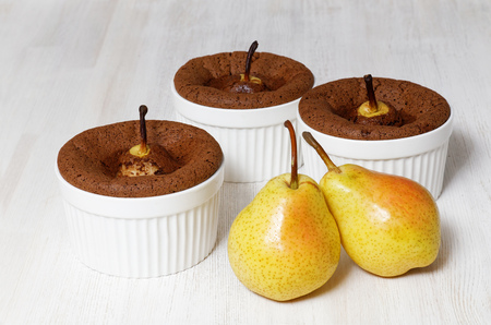 pear: Three chocolate-almond muffins with pears in white ceramic baking dish and two raw ripe pear fruit on white wooden table
