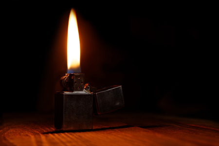 benzin: Old gasoline lighter with flame on wooden table against dark background
