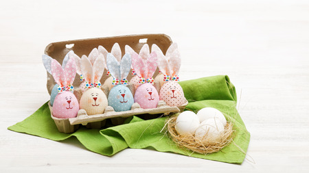 basket embroidery: Homemade Easter bunnies in egg box and eggs on a green cloth