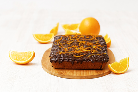shallow  focus: Chocolate and orange cake with orange peel on white wooden background. Shallow focus. Stock Photo