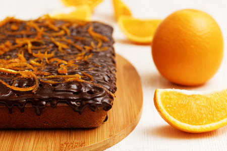 shallow  focus: Closeup chocolate and orange cake with orange peel on white wooden background. Shallow focus.