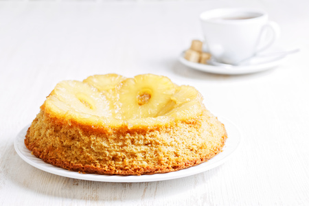 shallow  focus: Pineapple Upside Down Cake and cup of tea on white wooden table. Shallow focus. High key. Stock Photo