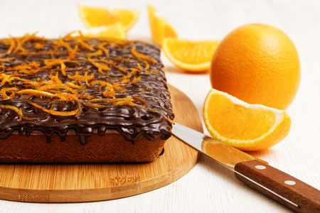 shallow  focus: Closeup chocolate and orange cake with orange peel near orange and knife on white wooden background. Shallow focus. Stock Photo