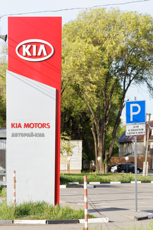 selling service: Ulyanovsk, Russia - May 22, 2016: Promotional stand with KIA sign near building KIA MOTORS selling and service center.