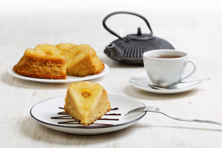 shallow  focus: Piece of pineapple Upside Down Cake, teapot and cup of tea on white wooden table. Shallow focus. Stock Photo