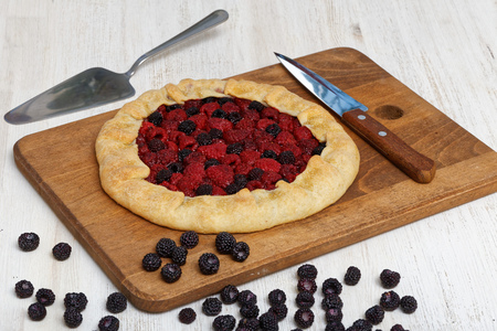 black raspberries: Homemade biscuit with red and black raspberries on a wooden cutting board. On a white wooden table scattered berries. Nearby lies the knife blade and stainless steel cake server.