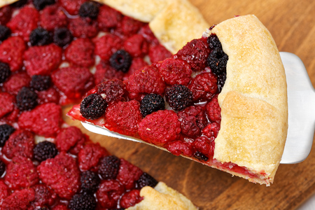 black raspberries: Piece of homemade galette with red and black raspberries on a stainless steel cake server. Stock Photo