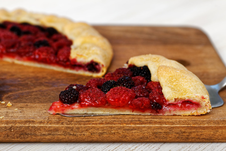 Closeup piece of homemade galette with red and black raspberries on a wooden cutting board. Shallow focus. Zdjęcie Seryjne