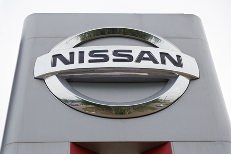 nissan: Ulyanovsk, Russia - July 20, 2016: Promotional stand with NISSAN sign near building Nissan service center, which provides vehicle maintenance, repairs and diagnostics.