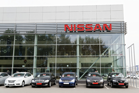 selling service: Ulyanovsk, Russia - July 20, 2016: Building of Nissan car selling and service center with Nissan sign. In front of the standing cars for sale.