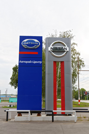 nissan: Ulyanovsk, Russia - July 20, 2016: Promotional stand with Nissan and Datsun signs near building of selling and service center which provides vehicle maintenance, repairs and diagnostics.