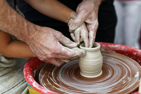 Closeup hands of the potter and his young apprentice  create a vase on a spinning potters wheel Stock Photo