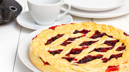 Homemade berry pie with cherries and raspberries on white wooden table. Shallow focus.