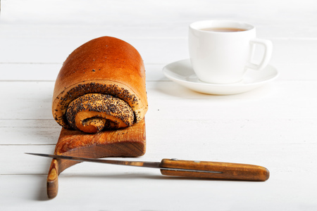 poppy seeds: Roll with poppy seeds and cup of tea on white wooden table. Stock Photo