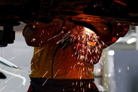 Worker of car service cleans old metal parts from rust using angle grinder. Sparks are flying in different directions.