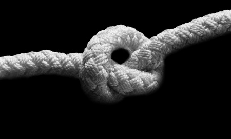 Closeup knot on a rope on black background. Black and white horizontal image.