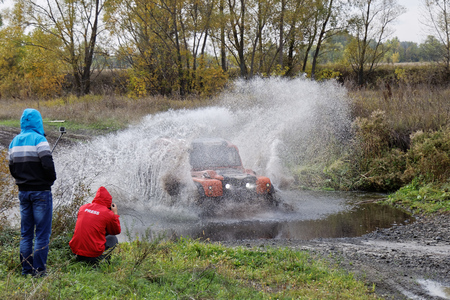 Ulyanovsk, Russia - September 24, 2016. Rally raid Hills of Russia. 4wd vehicle boosts water hurdle surrounded by splashes.