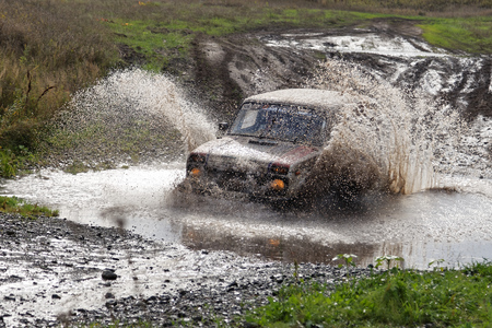 Ulyanovsk, Russia - September 24, 2016. Rally raid Hills of Russia. Rally car boosts water hurdle surrounded by splashes.