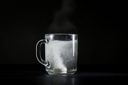 Effervescent tablet is dissolved in a cup of hot water. Dark background.