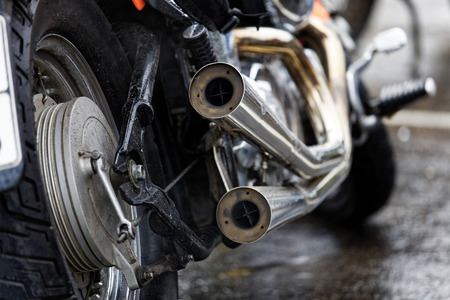 rear wheel: Closeup exhaust pipes and rear wheel of motocicle. Shallow focus. Stock Photo