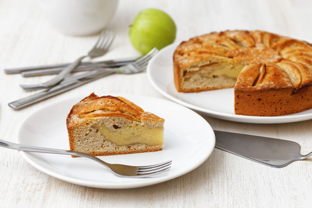 custard apples: Homemade apple custard pie topped with slices of apples and cinnamon on white wooden table. Shallow focus.