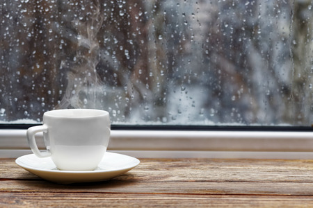 White steaming cup of hot tea or coffee on vintage wooden windowsill or table against window with raindrops on blurred background. Shallow focus. Archivio Fotografico