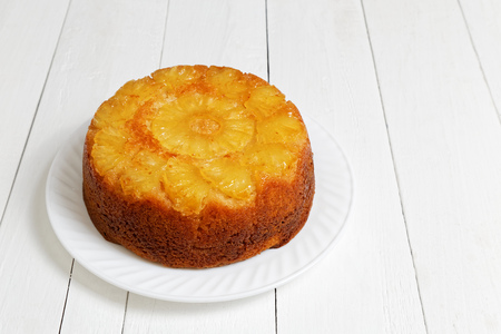 Homemade Pineapple Upside Down Cake on white wooden table. Shallow focus.
