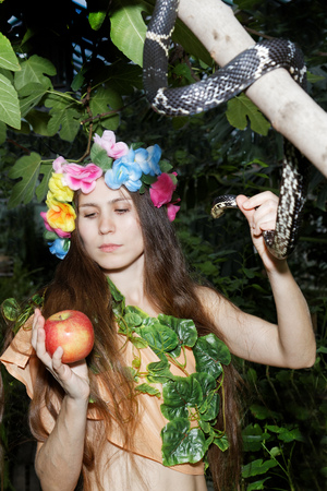 Young girl with floral wreath on her head holding an apple in one hand and a snake in the other. Foliage forest on dark background. Stock Photo