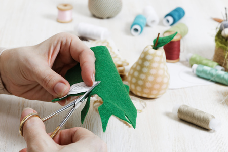Handicrafts. Closeup hands of the needlewoman hold scissors and cut out a piece of pattern for a handmade toy. There are handicraft materials on wooden table. Stock Photo - 75464267