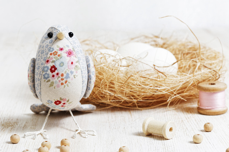 Closeup a handmade bird sewed from a cloth stands on a white wooden table surrounded by handicraft materials. Shallow focus and blurred background. Springtime handycraft.