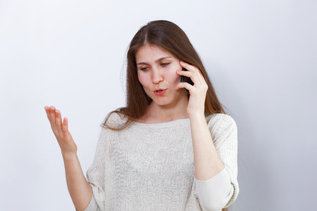 Portrait of young woman emotionally talking on the phone. Human reaction, expression. Grey background.