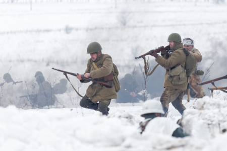 reenactment: Ulyanovsk, Russia - February 25, 2017:  Group of Russian Soviet Armed soldiers, reenactors during reenactment of World War II battle. Military-historical festival Immortal feat. Scene of battle. Editorial