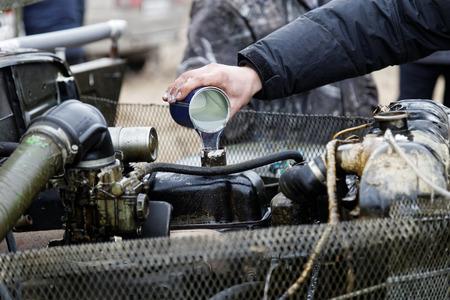 自動車整備士を注ぐエンジン オイル添加剤の古い自動車モーター