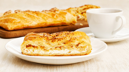 Piece of homemade puff braided pie from with cottage cheese, apples and raisins on white wooden table. Shallow focus. Stock Photo