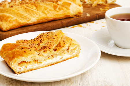 apple cinnamon: Piece of homemade puff braided pie from with cottage cheese, apples and raisins on white wooden table. Stock Photo