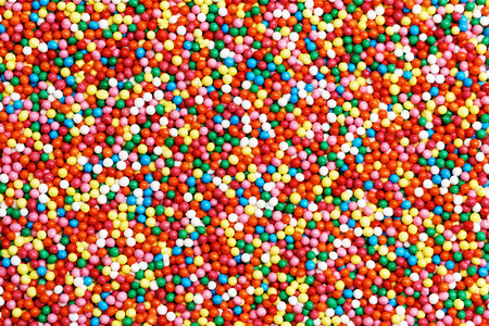 Background of colorful round-shaped candies filled with chocolate, multi-colored balls.