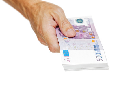 devaluation: A mans hand gives out a bundle of euro banknotes isolated on white. Financial concepts. Money in the hand.