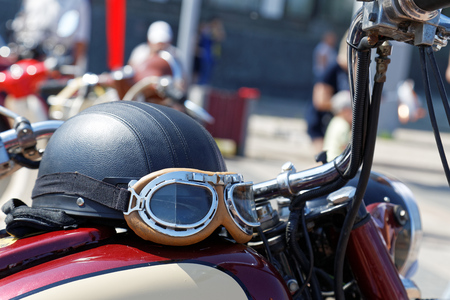 Black vintage moto helmet with glasses on motorcycle against blurred background Stock Photo